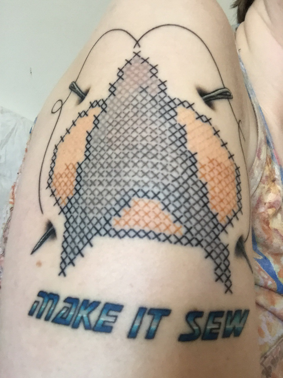 A cross stitched Star Trek bicep tattoo with the words,