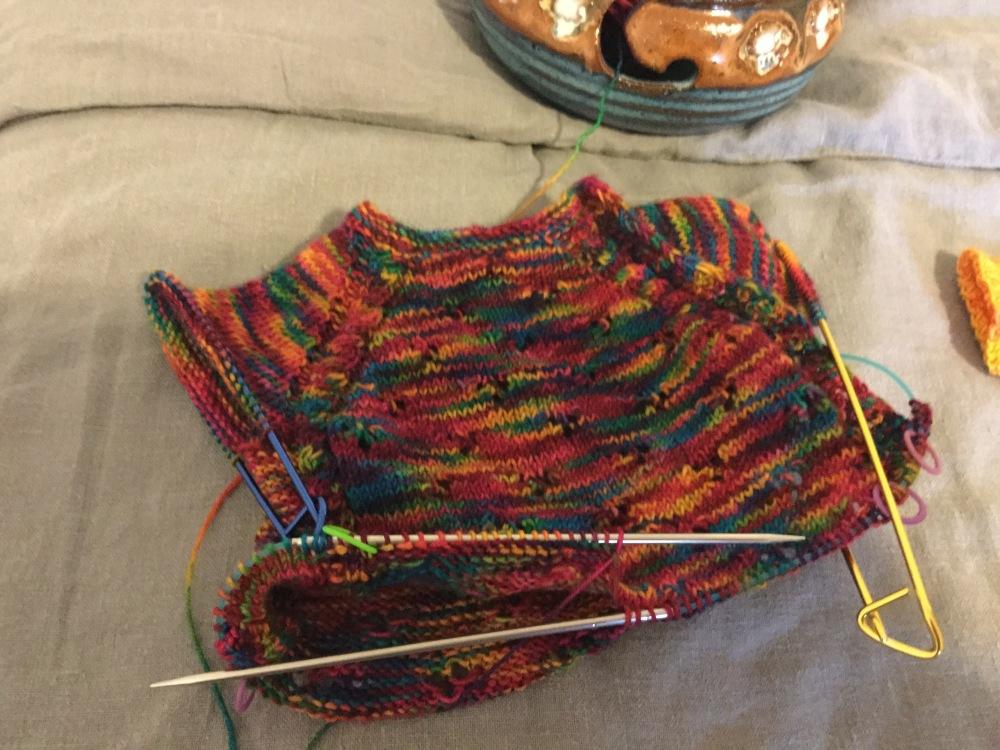 The top half of a sleeveless, rainbow baby onesie, still on the needles