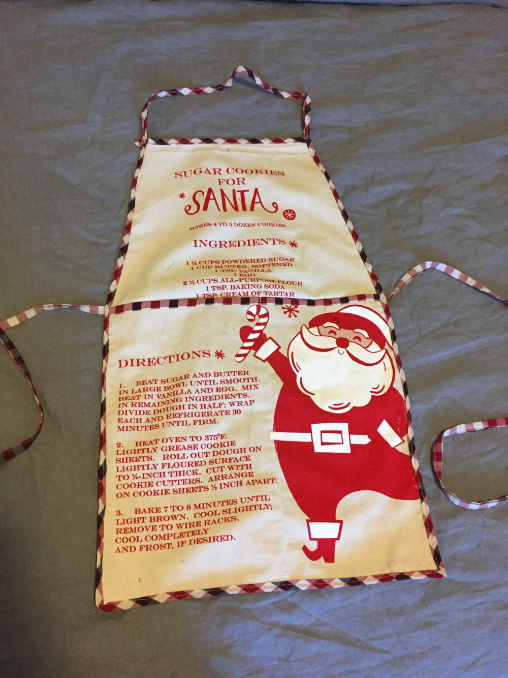 A handmade apron with an image of Santa and a sugar cookie recipe, trimmed with a red and white plaid fabric